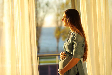 Side view portrait of a serious pregnant woman looking through a window at sunset 스톡 콘텐츠