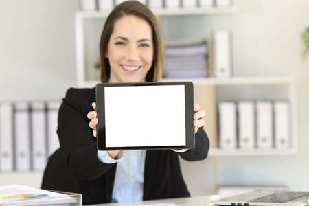 Happy office worker showing at camera blank tablet screen mock up Stockfoto