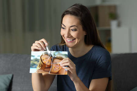 Crazy girl rebuilding a couple photo after breakup sitting on a couch in the night at home Stock Photo