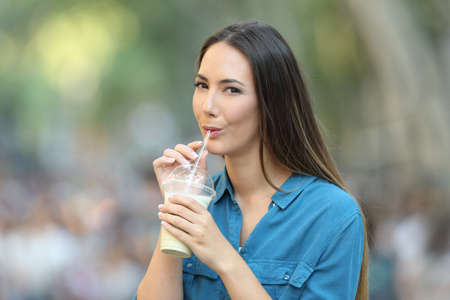 Happy woman drinking milk shake with a straw in the street looking at you Foto de archivo - 117941993