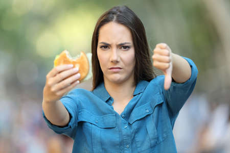 Front view of annoyed woman holding a burger with thumb down in the street