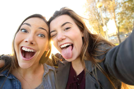 Two funny women joking taking selfies looking at camera in the street Imagens - 117941999