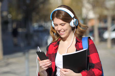 Happy student is listening to music from smart phone walking in the street