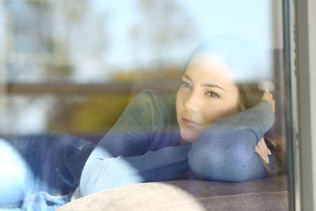 Serious woman thinking looking through a window sitting on a couch at home Stock Photo