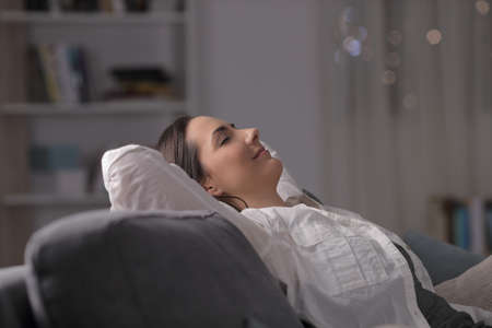 Side view portrait of a woman resting comfortably sitting on a couch in the night at home Stock Photo