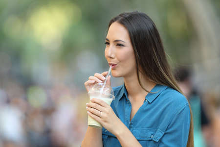 Happy woman sipping milk shake walking in the street Stock Photo