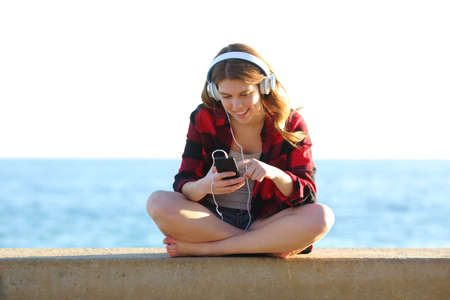 Full bofy front view portrait of a teenage girl browsing songs on smart phone listening to music on the beach Stock Photo