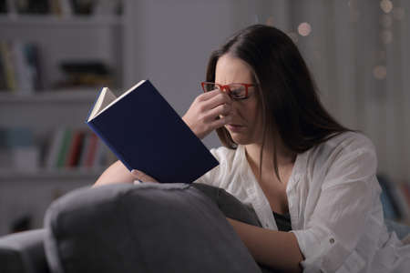 Lady wearing eyeglasses suffering eyestrain reading a book sitting on a couch at home in the night Stock Photo