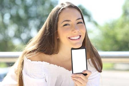 Happy woman showing blank smart phone screen outside in a park