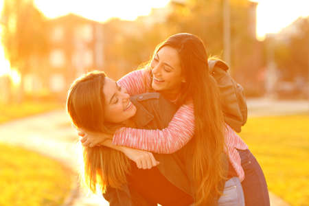 Two funny friends joking piggybacking in the street at sunset Reklamní fotografie