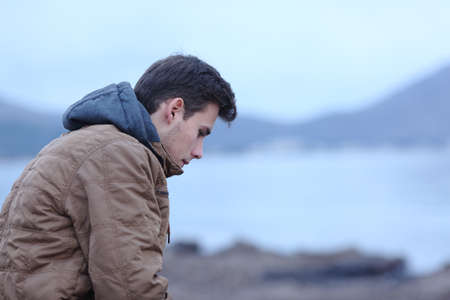 Side view ortrait of a sad man in winter on the beach complaining 免版税图像