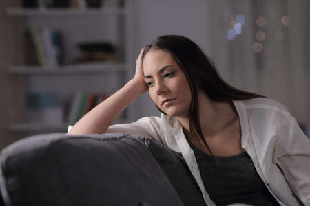Sad woman looks away sitting on a couch in the night at home