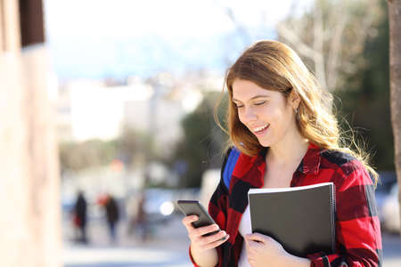 Happy student uses smart phone walking in the street a sunny day Фото со стока