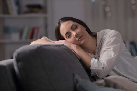 Woman sleeping sitting on a couch in the living room in the night at home