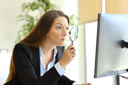 Suspicious office worker checking online content on computer using a magnifying glass Stock Photo