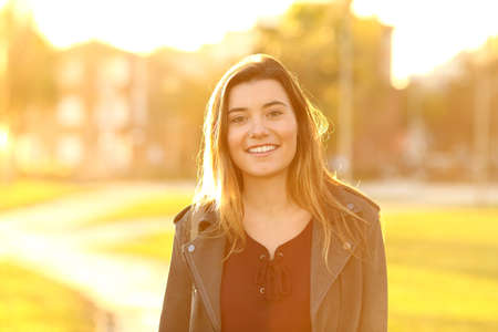 Front view portrait of a happy teenage girl looking at camera in a park at sunset Stock Photo
