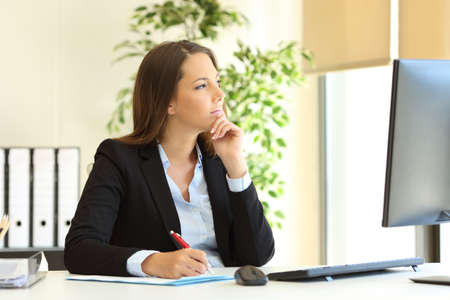 Pensive office worker looks away through a window at workplace