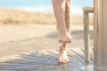 Close up of a woman cleaning feet in a shower after beach day