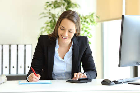 Office worker calculating budget using calculator and writing on a document