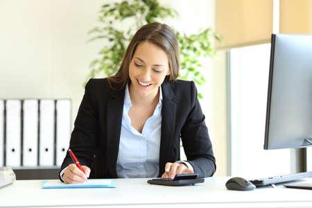 Trabajador de oficina calculando el presupuesto con la calculadora y escribiendo en un documento