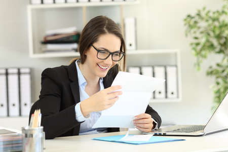Happy office worker reading a paper letter in a desktop Stock Photo