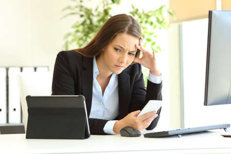 Worried office worker working using multiple devices on a desk