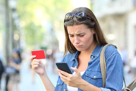 Worried girl having problem paying online with credit card and smart phone in the street Foto de archivo