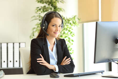 Confident office worker wearing headset looks at camera with folded arms at workplace