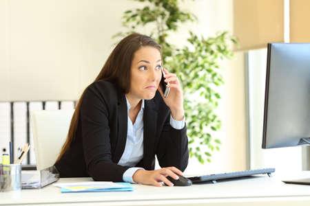 Impiegato confuso che chiama il telefono controllando il contenuto del computer