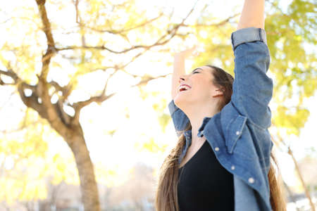 Excited woman raising arms celebrating success in a park with trees in the background