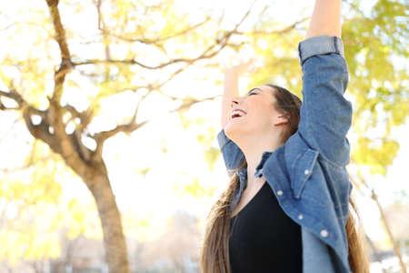 Mujer emocionada levantando los brazos celebrando el éxito en un parque con árboles en el fondo Foto de archivo