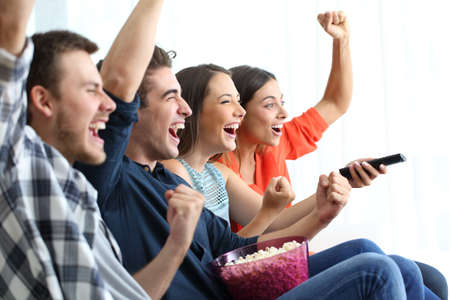 Four excited friends watching tv celebrating success sitting on a coucn at home