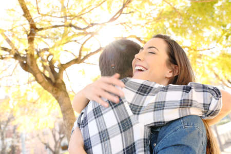 Happy couple or friends hugging in a park with trees in the background