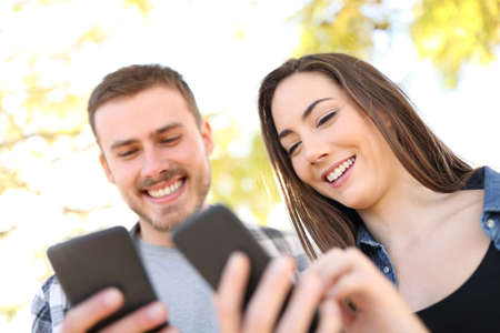 Portrait of a happy couple using their smart phones walking in a park Banque d'images - 117941921