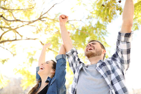 Excited couple celebrating success raising arms in a park with trees in the background Stock Photo