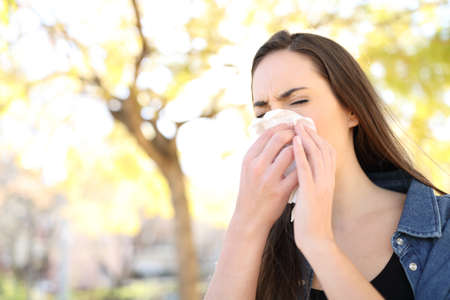 Sick woman sneezing covering nose with a wipe in a park