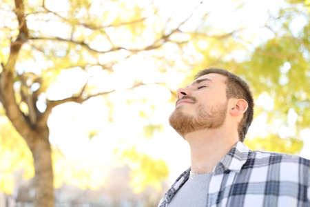 Hombre relajado está respirando aire fresco profundo en un parque con árboles en el fondo