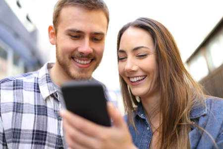 Front view portrait of a happy couple checking smart phone online content in the street Banque d'images - 117941962