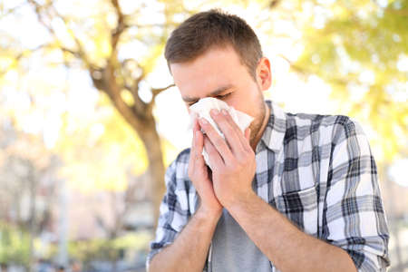 Allergic man sneezing covering nose with wipe in a park in spring season 스톡 콘텐츠