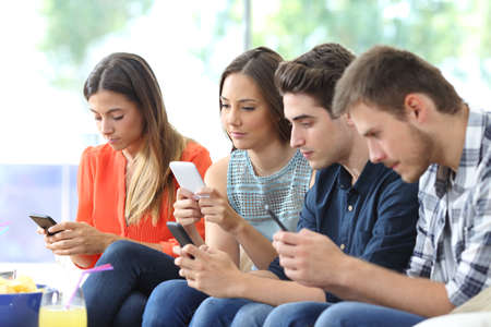 Group of serious friends using their smart phones sitting on a couch in the living room at home