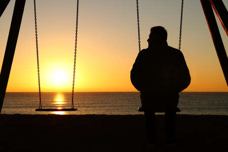 Back view backlighting silhouette of a man alone on a swing looking at empty seat at sunset on the beach in winter Standard-Bild - 117963685