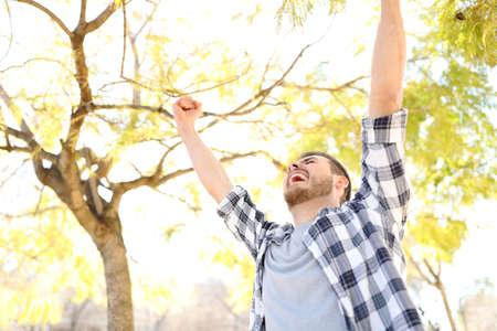 Ragazzo eccitato che celebra il successo alzando le braccia in un parco con alberi sullo sfondo Archivio Fotografico