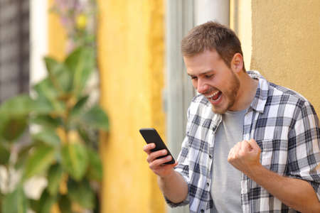 Excited man in the street checking smart phone celebrating good news Banque d'images - 118172685