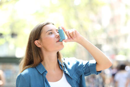 Asthmatic woman having an attack using asthma inhaler standing in the street