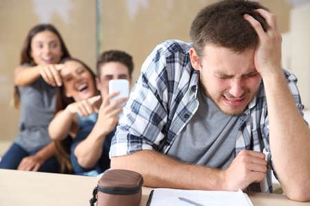 Sad teen complaining suffering cyber bullying from his mates