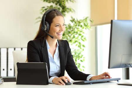 Comercializador de tele feliz trabajando en la oficina con computadora de escritorio y tableta Foto de archivo
