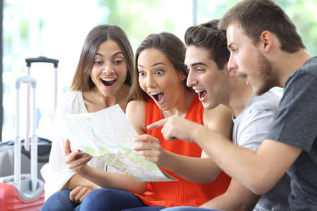 Group of surprised friends consulting map planning vacation sitting on a couch in the living room at home Stock Photo