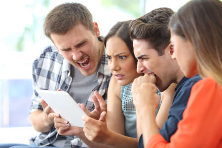 Angry group of friends watching media on tablet sitting on a couch in the living room at home