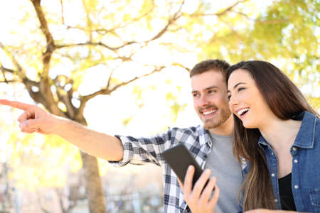 Happy couple holding smart phone pointing location standing in a park