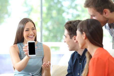Happy woman showing blank smart phone screen to her friends at home Banque d'images